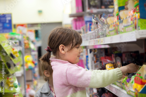 child in   toy store choosing   purchase