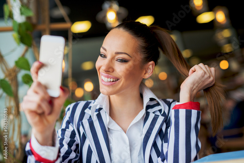 Fotobehang Kapsalon Gorgeous stylish young girl is making a selfie in a cafe while holding her ponytail.