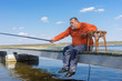 Elderly fisherman sitting on a pier with rod and ready to catch fish