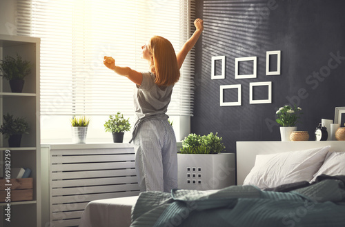 young   woman woke up in the morning in the bedroom by the window with her back Poster