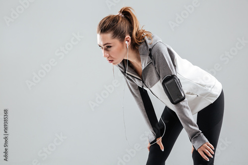 Tired young sportswoman in earphones resting while standing