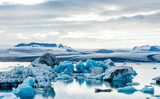 Glacial lagoon in Iceland, cloudy weather, mountains on the horizon. The glacial lake reflects the sky - 169385717