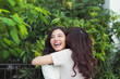 Happy young women friends well-dressed smiling while hugging together