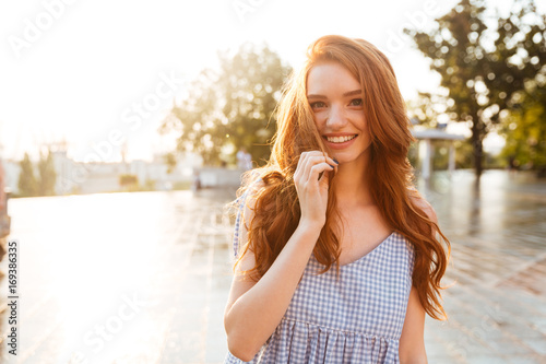 Happy pretty redhead girl with long hair looking at camera