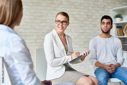 Portrait of beautiful female psychiatrist wearing glasses taking notes on clipboard while talking with  patients during group therapy session,