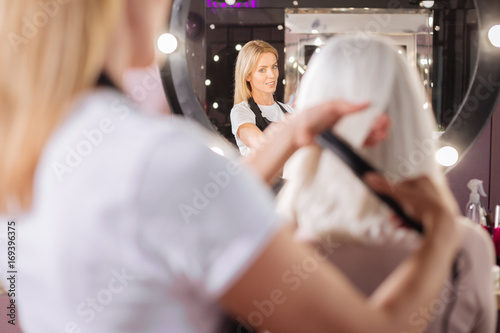 Fotobehang Kapsalon Hairdresser straightening clients hair with a straightening iron