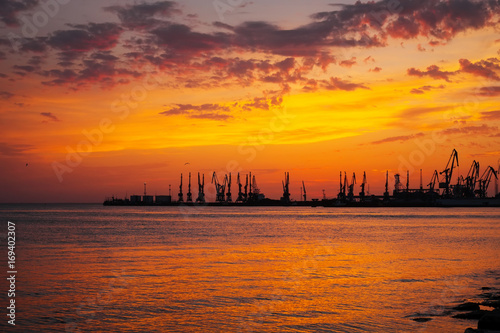 Papiers peints Brique Beautiful landscape with fiery sunset sky and sea. Harbor of Berdyansk during sunrise. Cranes silhouettes against fiery, orange and red sky.
