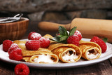Homemade crepes served with fresh raspberrries and powdered sugar on rustic wooden table