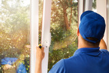 worker installing new plastic pvc window - 169409914