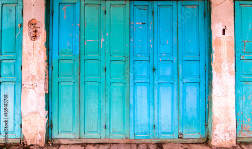Old house with vintage wooden blue cyan door and gray cement wall. Vintage blue cyan doors concept use for background.