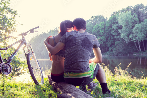 Foto op Canvas Aubergine couple near the river with bicycle