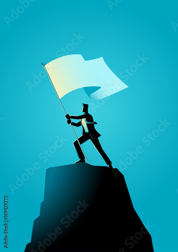 Businessman holding a flag on top of rock