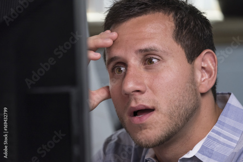 Man looking overwhelmed while looking at his computer