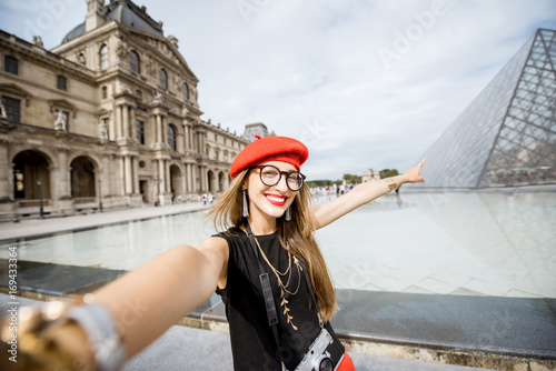 Young woman tourist in red cap making selfie photo in front of the famous Louvre Poster
