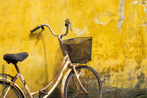In de dag Fiets Old bicycle against old yellow wall on a street of Hanoi old town, Vietnam.