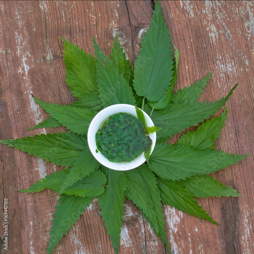 Herbs tea from  leaves of a nettle on a wooden surface. Top view