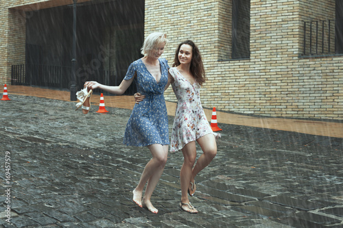 Women are walking in the rain in the city, they are smiling and happy Poster
