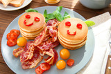 Creative tasty breakfast with pancakes and bacon on table