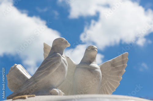Two white pigeons of marble against a blue sky with clouds
