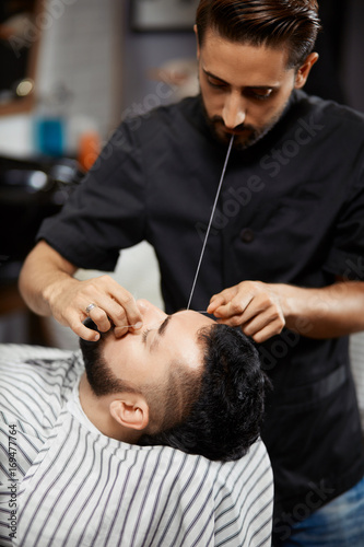 Professional hairdresser doing correction of bread in barbershop.