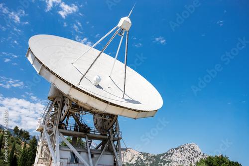 Plexiglas Large radio telescope near mountains at daytime