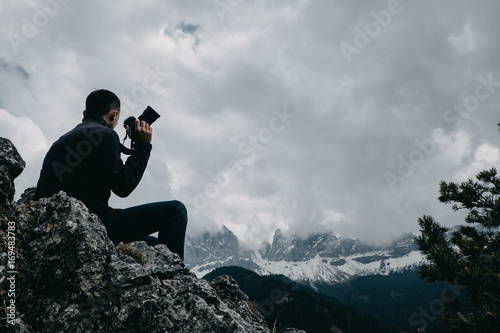 Fotobehang Donkergrijs Man traveler with digital camera taking a photo