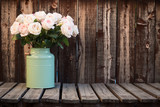 Pink roses in a green bucket style container on a wooden plank table. - 169485925