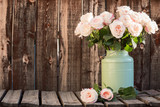 Pink roses in a green bucket style container on a wooden plank table. - 169485931