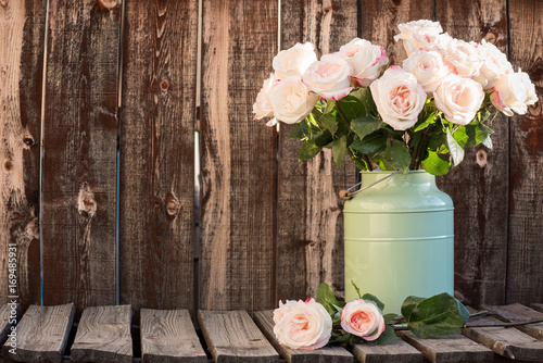 Fototapeta Pink roses in a green bucket style container on a wooden plank table.