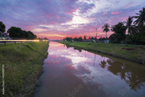 Fotobehang Purper Colorful sky with clouds during sunset at canal
