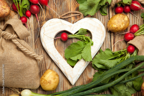 Poster Potatoes and radishes on a wooden background