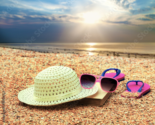 Beach scene. Sun straw hat, book, flip flop sandals and sunglasses lying on sea coquina shells on the beach at sunrise