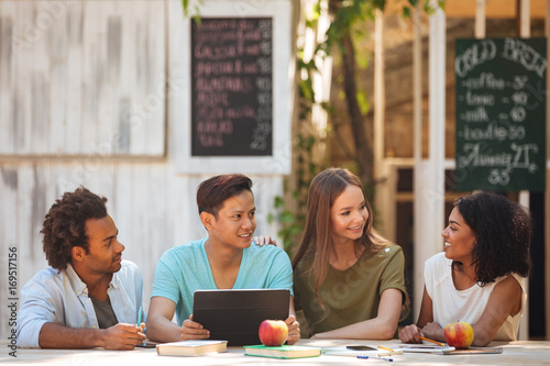Four young frineds sitting by the table outdoors