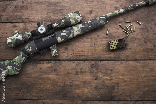Small caliber 22 long rifle with an optical sight and cartridges in camouflage tape