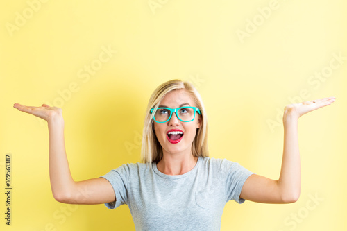 Young woman reaching and looking upwards on a yellow background