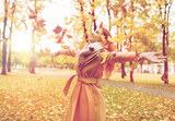 happy woman having fun with leaves in autumn park - 169565389