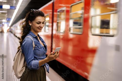 Piękna kobieta używa jej telefon komórkowego na metro platformie.