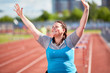 Successful over-size woman raising hands after crossing finish