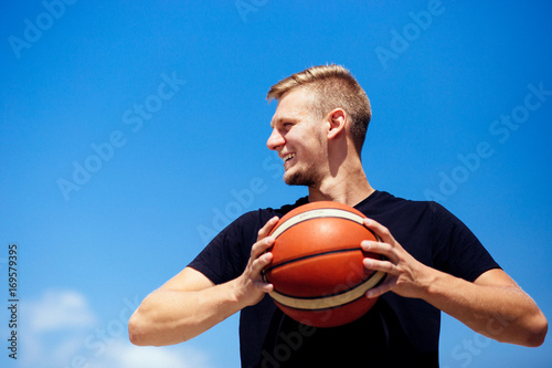 Fotobehang Basketbal Handsome tall blonde person holding a ball and looking at the court smiling, blue sky background