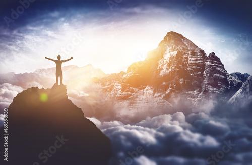 Leinwanddruck Bild Bergsteiger erlebt absolutes Gipfelglück hoch über den Wolken