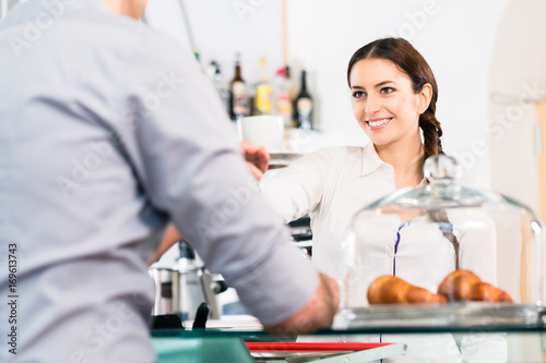Beautiful waitress serving male customer with a cup of coffee for breakfast indo Poster