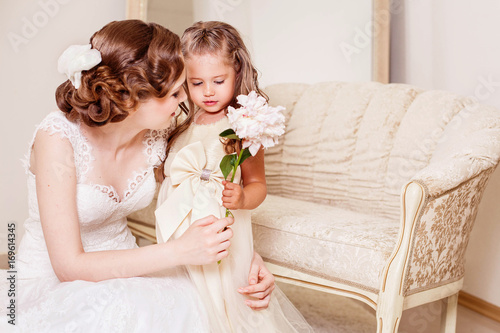 Shy flower girl gives a flower to bride. Wedding. Just married. Kids at the wedding. Wedding hairstyle