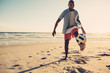 African man playing with soccer ball at beach