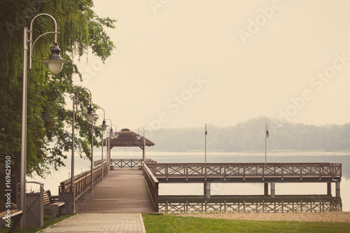 Fotobehang Pier Vintage photo, Footpath and wooden pier at lake on cloudy day