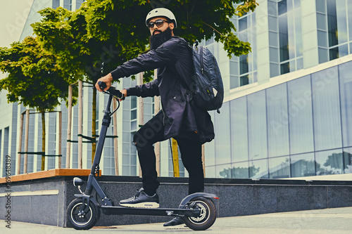 A man posing on electric scooter. Poster