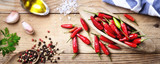 Red chili peppers, peppercorns, parsley, garlic and extra virgin olive oil on wooden background