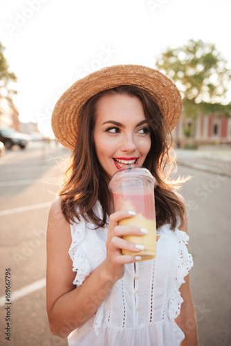 Poster Beautiful young woman outdoors drinking juice