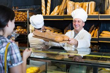 Woman choosing fresh baguette from baker