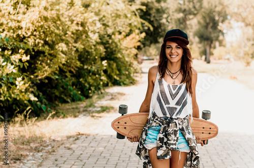 Fotobehang Skateboard Woman holding longboard behind her back.