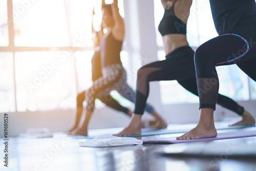 Leinwanddruck Bild Women exercising in fitness studio yoga classes